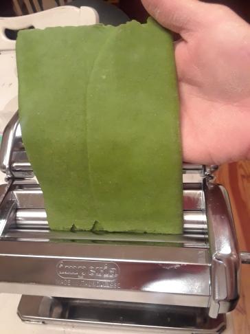 Green pasta dough in machine